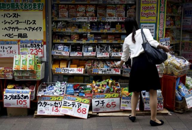 A shopper looks at items outside a discount drug store at a shopping district in Tokyo, Japan, July 29, 2015. REUTERS/Yuya Shino