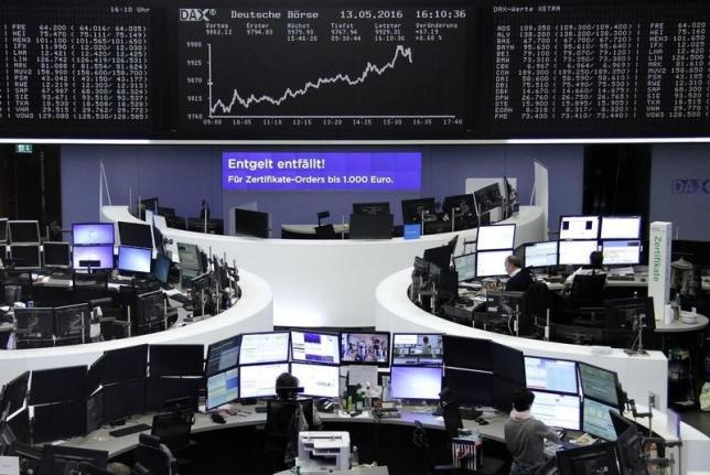 Traders work at their desks in front of the German share price index, DAX board, at the stock exchange in Frankfurt, Germany, May 13, 2016.     REUTERS/Staff/Remote